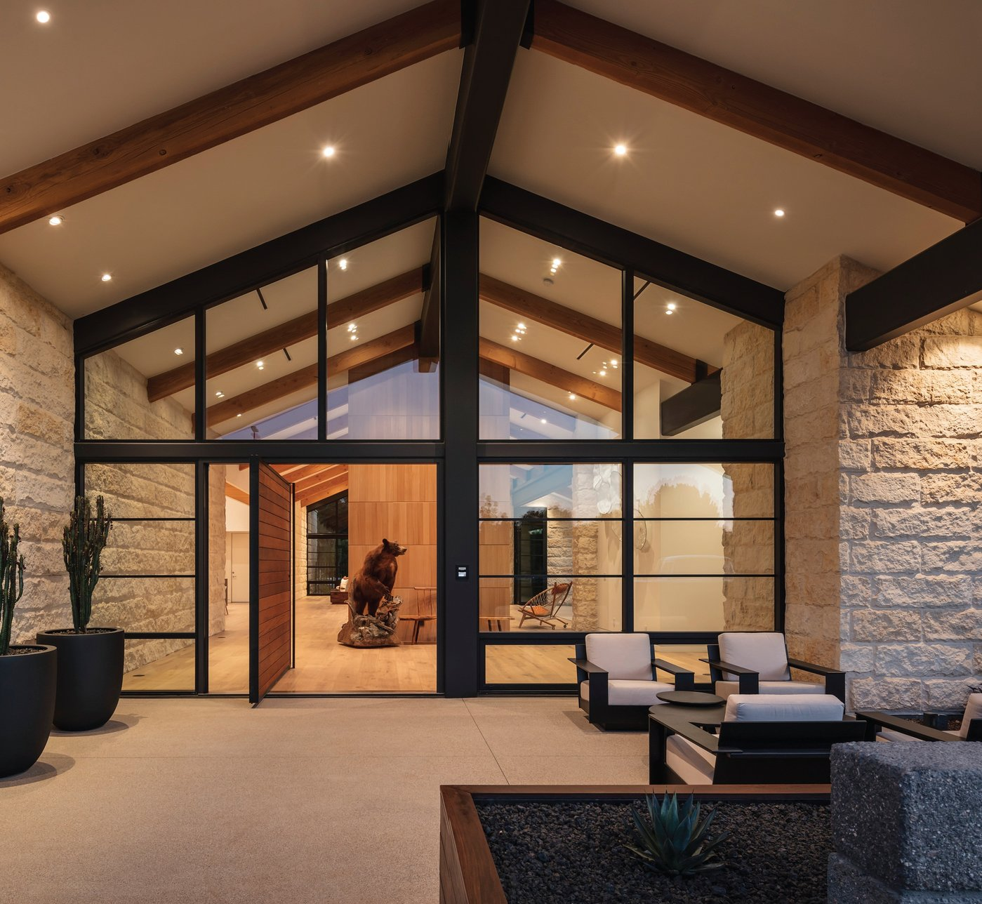 The main entry door is an 8-foot-by-8-foot pivot door made of steel and ipe wood. Once past the foyer, the house opens up to the main great room for entertaining. Photographed by Roehner   Ryan Photography