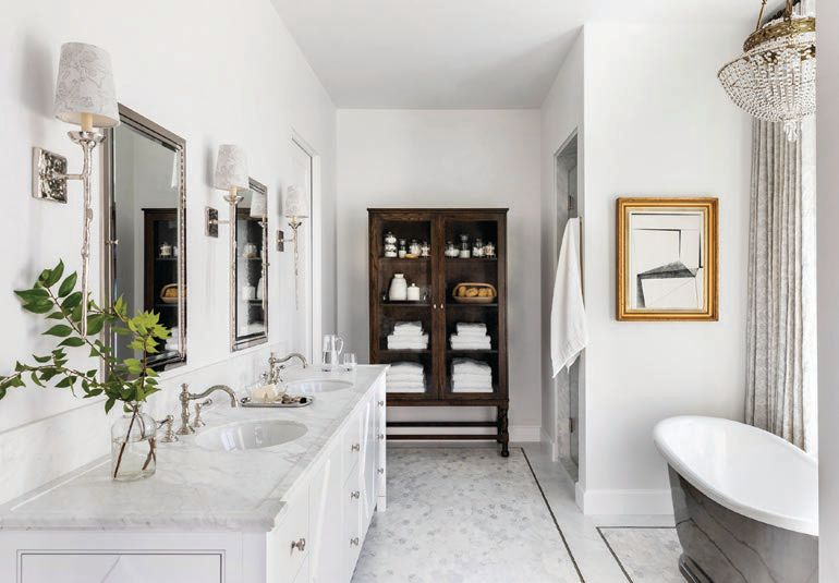 In the light-filled master bathroom, a Catchpole & Rye tub sits under an antique European chandelier from Houston's own Brown House and Wares. Vaughan wall sconces add even more light. PHOTOGRAPHED BY JULIE SOEFER