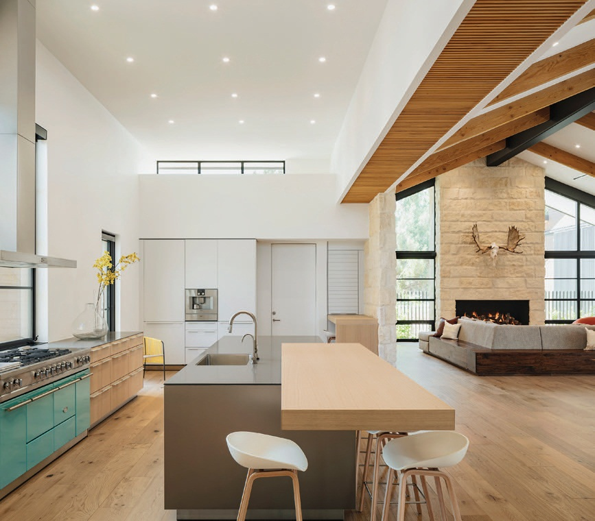 A textured wood ceiling delineates the kitchen area from the main living and dining areas. The island is an oak cantilevered section that provides seating on each side Photographed by Roehner   Ryan Photography