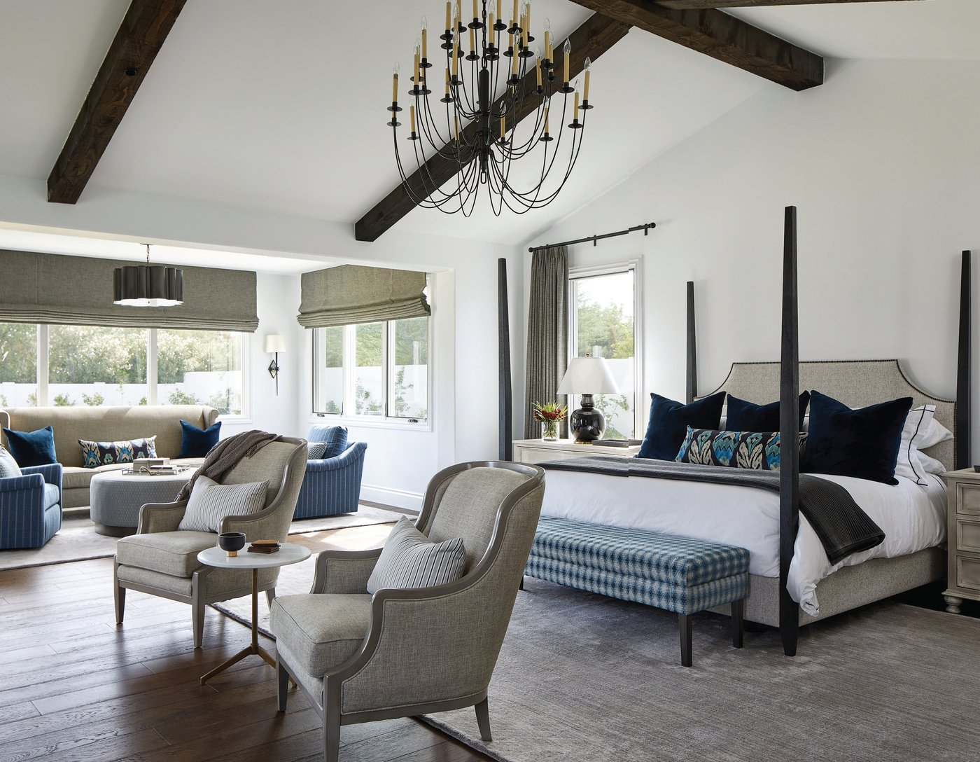 With its separate seating area, wood beams and fireplace, there is no detail missing in this cozy main bedroom. Photographed by Laura Moss Photography